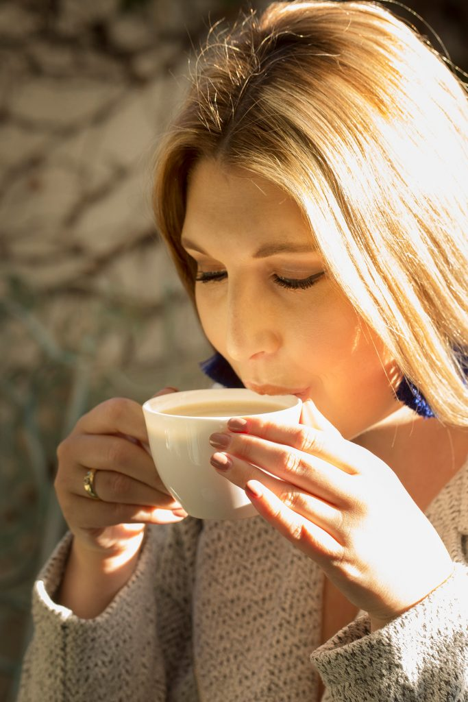 The Glam Green Girl sipping a cup of coffee