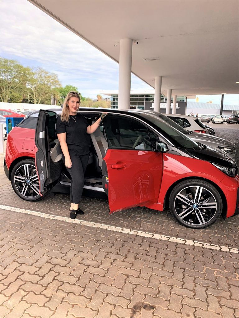 The Glam Green Girl with the BMW i3 that is being featured in her blog post.